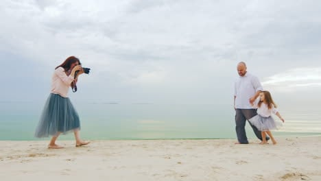 Family-Photo-Shoot-Mom-Takes-Pictures-Dad-And-Daughter-On-The-Beach
