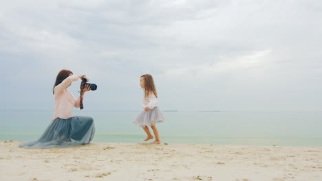 Young-Photographer-Mother-Taking-Photo-of-Daughter-on-Beach