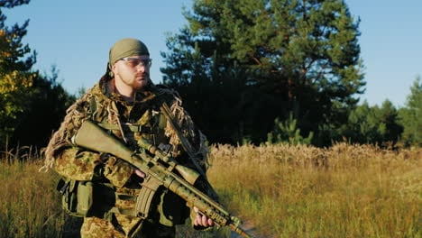 A-Man-In-A-Camouflage-Bandanna-And-Walking-Along-A-Country-Road-In-The-Hands-Holding-Weapons-Slow-Mo