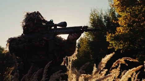 Sniper-In-Camouflage-Clothing-Takes-Aim-The-Sun-s-Rays-Shine-Through-In-The-Back-And-Arms