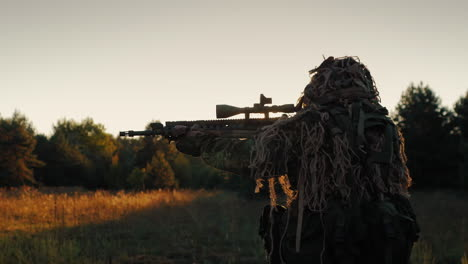 Sniper-In-A-Camouflage-Outfit-Moved-Cautiously-Looks-Through-The-Scope-Of-Weapons-At-Sunset