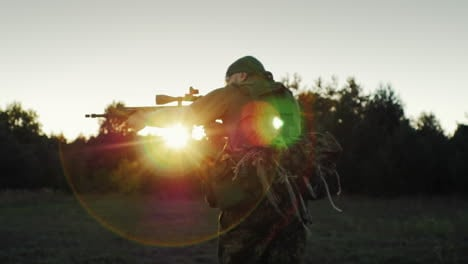 A-Man-In-Military-Uniform-Attacked-Running-With-A-Gun-In-The-Sunset-Back-View-Steadicam-Slow-Motion-