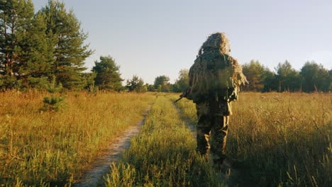 Armed-Men-In-Camouflage-Walking-Along-A-Country-Road-Back-View