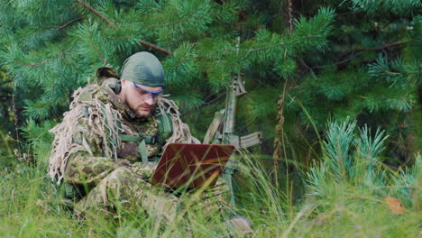 Armed-Men-In-Camouflage-Sitting-In-The-Bush-Uses-A-Laptop