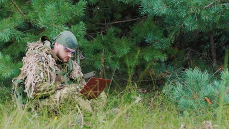 A-Man-In-Military-Uniform-Sitting-In-The-Woods-Enjoying-The-Pclaptop