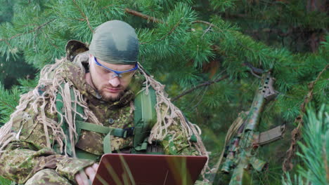Portrait-Of-Military-Man-Sitting-In-The-Woods-Dressed-In-Camouflage-It-Uses-Laptop