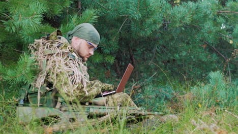 Armed-Men-In-Camouflage-Sitting-In-The-Woods-It-Uses-Laptop