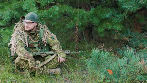 The-Young-Man-In-Uniform-With-A-Weapon-In-His-Hands-He-Is-Sitting-In-The-Forest-Resting-Looking-Arou