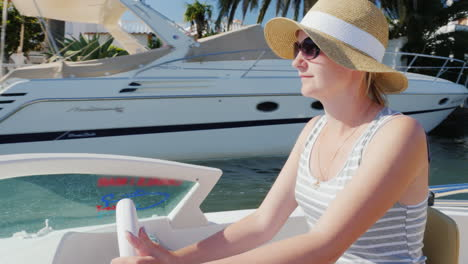 Young-Woman-Tourist-With-Sunglasses-Sitting-At-The-Controls-Of-A-Small-Boat-Floating-Empuriarava-Cha