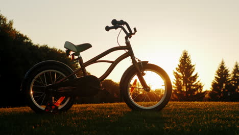 Children-s-Bicycle-Standing-On-A-Green-Lawn-On-The-Background-Of-The-Setting-Sun-Concept---Children-