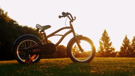 Children-s-Bicycle-On-Green-Grass-At-Sunset-Concept---Nostalgia-Childhood-Dreams