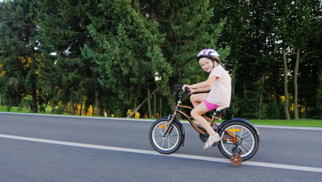 Funny-Girl-Five-Years-Old-Riding-A-Bicycle-With-Extra-Wheels-Smiling