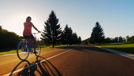 Young-Woman-Riding-A-Bicycle-In-The-Sunset-Back-View-Slow-Motion-Video