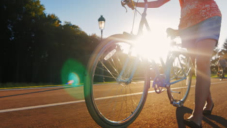 A-Woman-Leads-A-Bicycle-In-The-Picture-One-Can-See-The-Legs-And-The-Wheel-The-Sun-s-Rays-Shine-Throu