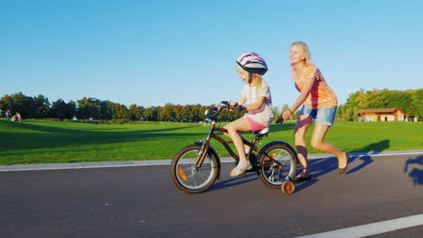 Mom-Teaches-Girl-To-Ride-A-Bike-Concept---Help-And-Support-For-Parents-A-Happy-Childhood