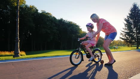 Mom-Plays-With-Her-Daughter-Teaching-Her-To-Ride-A-Bicycle-At-Sunset-Background