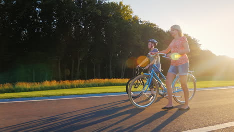 Woman-And-Son-Walking-In-The-Park-With-Bikes-Slow-Motion