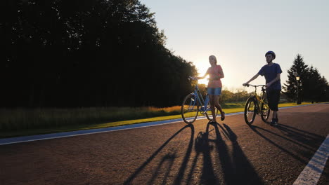A-Woman-Walks-With-Her-Son-Teenager-Lead-Bike-At-Sunset