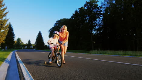 Active-Games-With-Children-Woman-Learns-The-Girl-To-Ride-A-Bike-Enjoys-The-Success-Of-A-Child