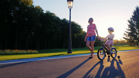 Mother-And-Daughter-Walking-In-The-Park-Mother-Holds-Her-Hand-A-Child-Riding-A-Bicycle-Near