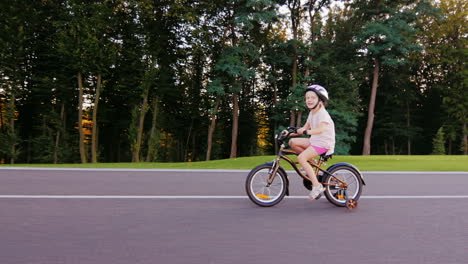 Girl-Five-Years-In-A-Helmet-Riding-A-Bike-In-The-Well-Kept-Park-On-A-Background-Of-Trees