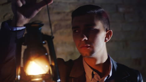 Scared-Young-Man-In-A-Dark-Hallway-Holding-An-Oil-Lamp-In-His-Hand-Dressed-In-A-Suit