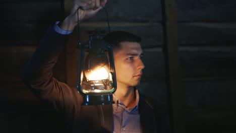 The-Frightened-Man-In-A-Suit-Standing-In-A-Dark-Room-Covers-Himself-Around-A-Kerosene-Lamp