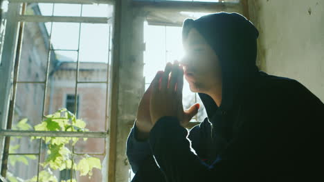 Teenager-In-The-Hood-Sits-On-A-Window-Sill-Holding-His-Hands-In-His-Head-To-Pray-In-The-Rays-Of-The-