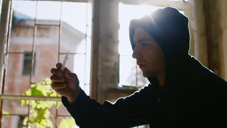 To-Overcome-Drug-Addiction-A-Young-Man-Throws-A-Syringe-Sitting-At-A-Window-In-The-Sun