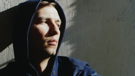 Upset-Young-Hooded-Man-Sitting-Near-The-Window-The-Sun-Is-Shining-Spots-On-His-Face