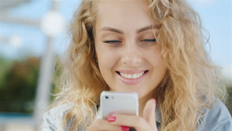 Portrait-Of-An-Attractive-Young-Woman-Looking-At-Phone-Screen-Smiling