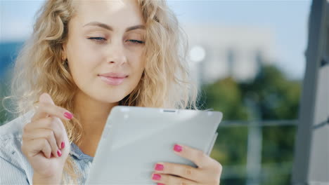 Portrait-Of-An-Attractive-Young-Woman-Uses-Tablet-On-A-Summer-Area-In-The-Cafe-Smiles-Positive-Emoti