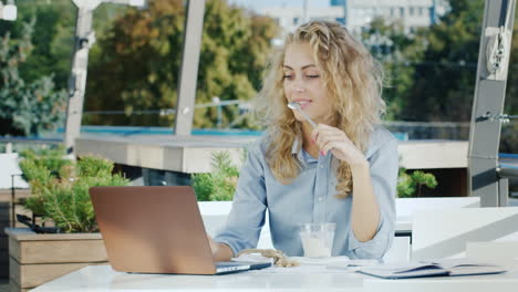Young-Business-Woman-Working-In-A-Cafe-On-The-Summer-Ground-He-Eats-Ice-Cream-Uses-A-Laptop