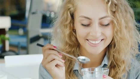 Attractive-Young-Woman-Eating-Ice-Cream-In-Cafe-Smiling-At-The-Camera
