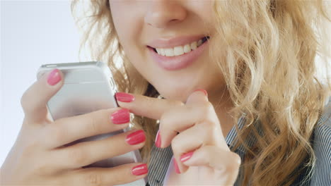 Woman-Typing-On-Smartphone-And-Smiling-Close-Up-Of-Hands-In-The-Frame-Can-Be-Seen-With-A-Phone-And-T