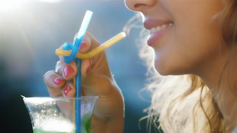 Young-Woman-Stirs-The-Drink-In-The-Glass-In-The-Picture-Visible-Lips-And-Hair-In-Which-The-Sun-Shine