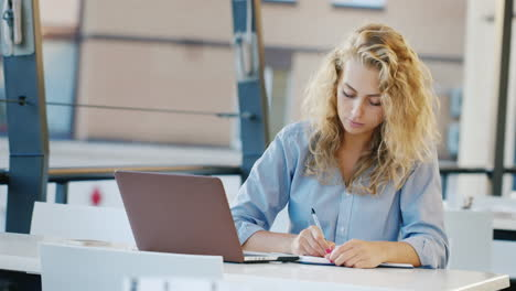 Attractive-Young-Woman-Working-On-The-Site-In-Summer-Kaye-Uses-Laptop-Takes-Notes-In-A-Notebook
