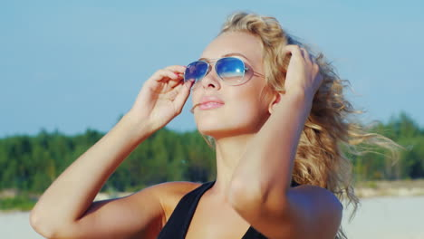 An-Attractive-Young-Woman-In-Sunglasses-Posing-At-The-Camera-At-The-Beach-Smiling