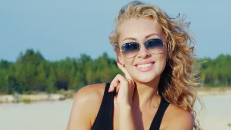 Young-Woman-In-Sunglasses-Smiling-At-The-Camera-The-Wind-Playing-With-Her-Hair