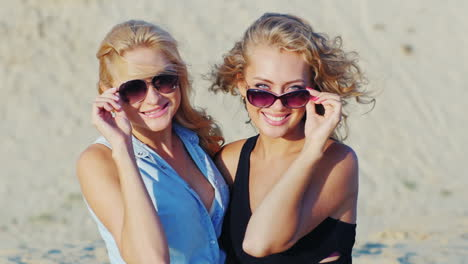 Two-Young-Women-Posing-For-The-Camera-Smiling-On-The-Beach-On-A-Sunny-Day
