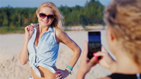 Sexy-Blonde-Woman-In-Sunglasses-Posing-For-His-Girlfriend-Her-Phone-Is-Photographed-On-The-Beach