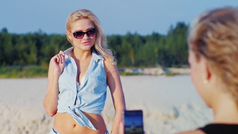 Sexy-Blonde-Woman-In-Sunglasses-Posing-For-His-Girlfriend-Her-Teléfono-Is-Photographed-On-The-Beach