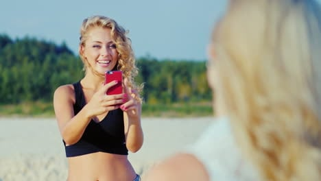 Young-Woman-Photographed-With-A-Smartphone-To-His-Girlfriend-On-The-Beach-Showing-Gestures-Of-Approv