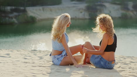 Two-Female-Friends-Relaxing-On-The-Shores-Of-Scenic-Lake