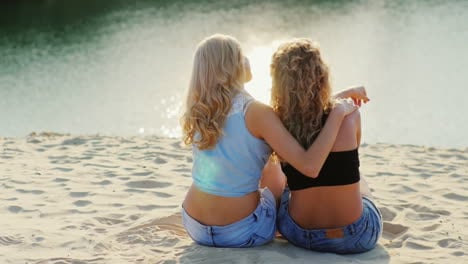 Two-Friends-Women-Sitting-On-The-Beach-Admiring-The-Beautiful-Scenery