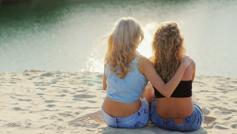 Romantic-Couple-Of-Two-Women-Sitting-In-An-Embrace-On-The-Beach-Gently-Hugging