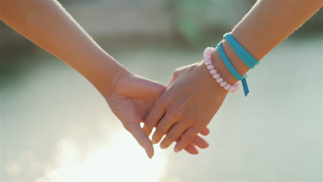 Two-Woman-Tenderly-Hold-Hands-Romantic-Couple