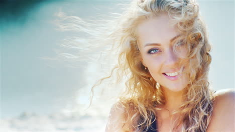 Young-Woman-Smiling-Into-The-Camera-Playing-With-Her-Beautiful-Hair-On-The-Beach-Portrait