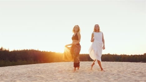 Two-Young-Women-In-Beautiful-Dresses-Are-On-The-Beach-At-Sunset-Wind-Plays-A-Beautiful-Dress-Steadic