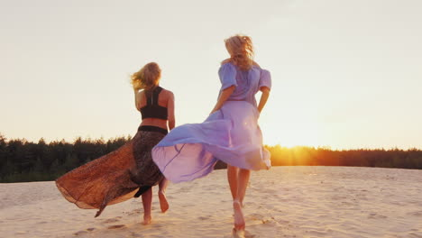 Two-Women-In-Light-Dresses-Run-Toward-The-Sun-Concept-Women-s-Dreams-Health-Happiness-Steadicam-Slow